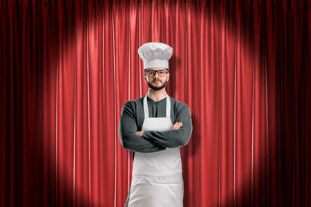 Chef wearing kitchen apron and chef hat on red stage curtains background Reklamní fotografie