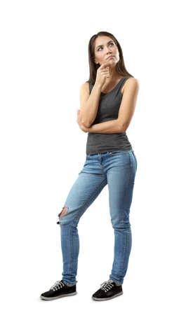 Woman in gray top and blue jeans standing with thoughtful expression on her face and with hand on her chin looking up isolated on white background. Stock Photo