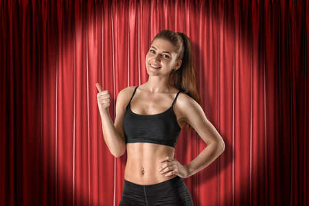 Young fit smiling girl in sport crop top and shorts standing in half-turn, looking at camera and doing thumbs-up, lit up by spotlight near red curtain. Reklamní fotografie
