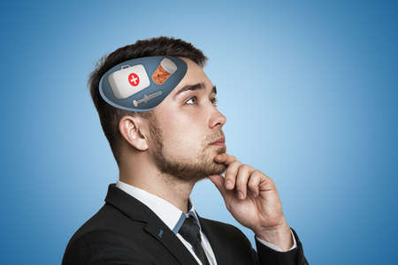 Young businessman thinking with first aid medical box, pills jar and syringe in his head on blue background