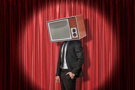 Businessman with vintage tv set instead of head on red stage curtains background Reklamní fotografie