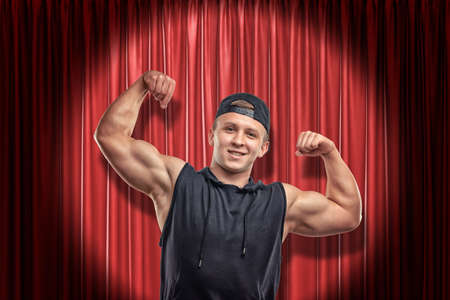 Young muscular man in black sport clothing smiling and showing biceps on red stage curtains background