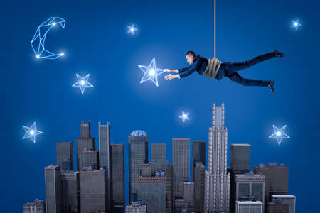 A businessman hanging on a rope above a night city and trying to catch a star in the sky.