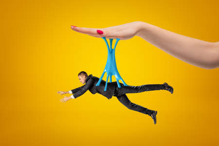 Side view of little man in suit hanging on blue sticky slime stuck to big womans hand above on yellow background.
