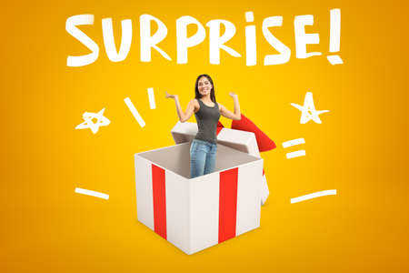 Young smiling woman in sleeveless top and blue jeans appearing from big white gift box on yellow background with title SURPRISE