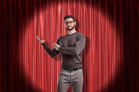 Front crop view of young handsome man in casual clothes and glasses standing in spotlight against red stage curtain and making presenting gesture at it.