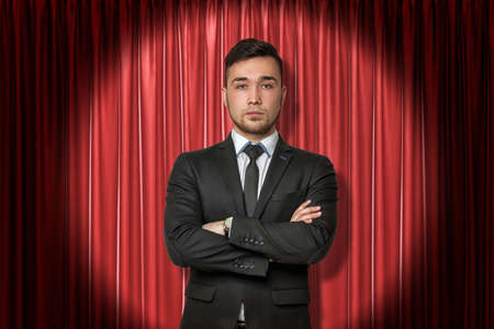 Young businessman on red stage curtains background
