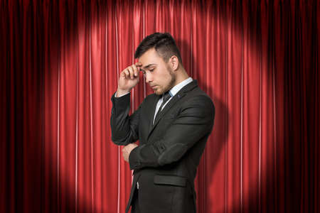 Young businessman thinking on red stage curtains background