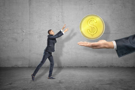 Side full length view of little businessman reaching out for big gold coin levitated above huge hand emerging from right.