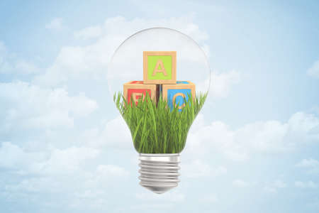 3d closeup rendering of lightbulb with three ABC blocks lying on green grass inside bulb against blue sky with clouds.
