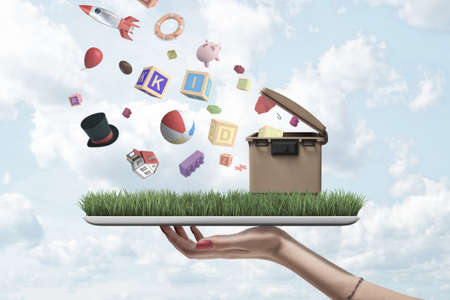 Side close-up of womans hand holding digital tablet with green grass and trash can on screen and with misc objects falling from sky on to grass.