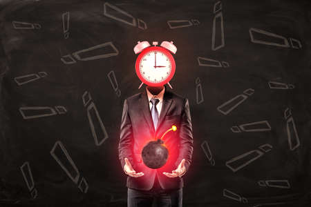 Businessman with clock instead of head holding ball bomb with fuse on black background with exclamation sign pattern