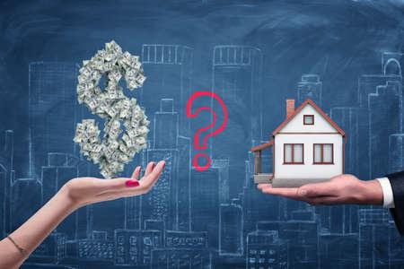 Una mano femminile con un simbolo del dollaro su di essa e una mano maschile con una piccola casa su uno sfondo di città di gesso. Archivio Fotografico