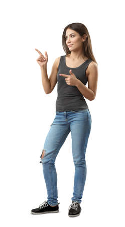 Young woman in sleeveless top and jeans standing in half-turn with both hands bent and index fingers pointing sideward isolated on white background.