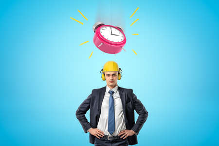Front waist-deep image of businessman standing, hands on hips, wearing yellow hard hat with big pink alarm clock ringing in air above.