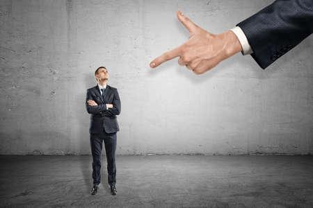 Vorderansicht in voller Länge des kleinen Geschäftsmannes, der steht und auf die riesige Hand blickt, die mit dem Zeigefinger auf ihn zeigt. Standard-Bild