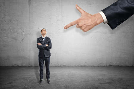 Vue avant sur toute la longueur du petit homme d'affaires debout et regardant une énorme main pointant l'index vers lui. Banque d'images