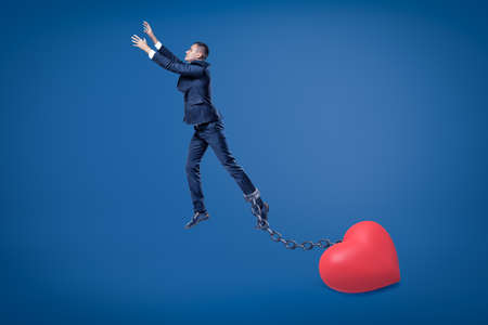 Side view of businessman in mid-air chained to big Valentine heart on the ground.