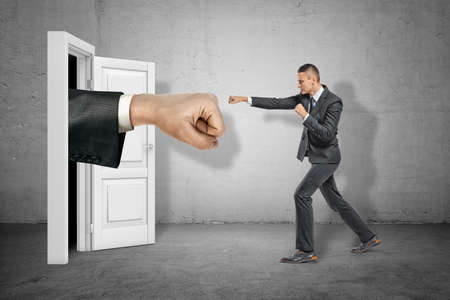Big stretched fist appearing through white doorway and businessman making kicking gesture on grey wall background
