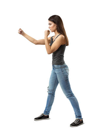 Side view of young attractive woman in gray sleeveless top and blue jeans posing with arms in figthing position isolated on white background.