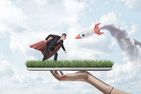 Female hand holding grass board with small businessman in red superman mask and cloak with silver red rocket on blue sky background