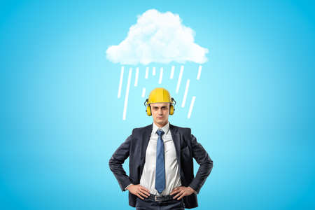 Front crop image of businessman in yellow hard hat with ear defenders, standing with hands on hips under white raining cloud.