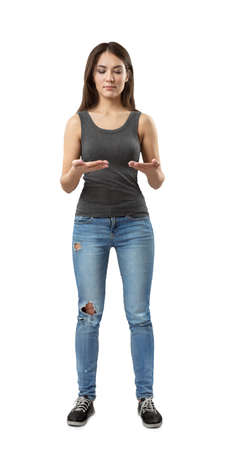 Front view of young woman in gray top and blue jeans standing with elbows bent as if holding invisible tablet isolated on white background.
