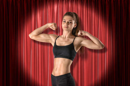 Crop image of young fit woman in crop top, standing in half-turn in spotlight at red stage curtain, raising hands and showing her biceps.