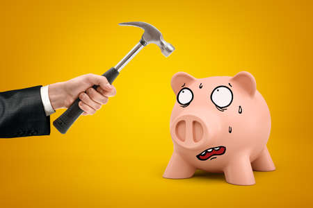 Male hand holding hammer over pink cartoon face piggy bank on yellow background