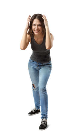 Front view of beautiful woman in gray top and blue jeans standing and leaning forward, with hands on head, smiling and wrinkling nose on white background.