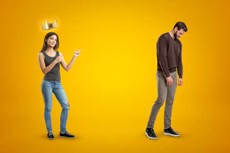 Young happy brunette girl in casual clothes with a golden crown above and a sad man in casual clothes on yellow background Stock Photo