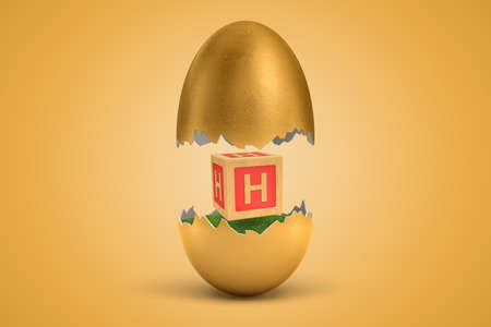 3d rendering of gold egg cracked in two, upper half levitating in air, lower on ground, with small wooden ABC block with letter H on sides between two halves. Stock Photo