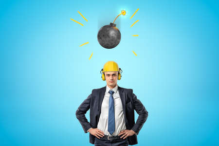 Crop image of businessman in yellow hard hat with ear defenders, standing with hands on hips, and round bomb falling down on him.