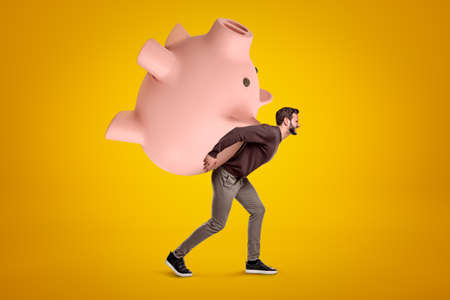 Young man in casual clothes carrying a big pink piggy bank on his back on yellow background