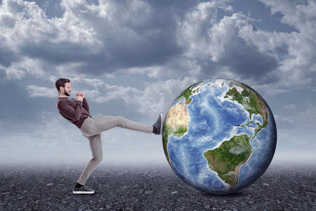 Full length side view of young man in casual clothes kicking huge Earth globe lying on ground under gray cloudy sky.