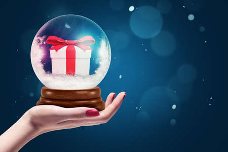 Closeup of womans hand holding crystal ball with snow and little gift box inside on blue background with copy space.