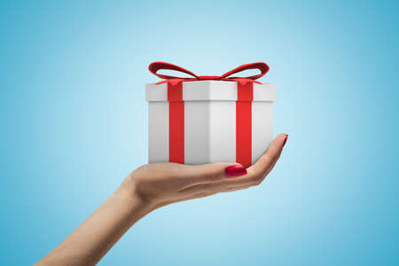 Side closeup view of womans hand holding white gift box tied with red ribbon on light blue background.