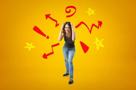 Young girl in casual clothes making brain explosion gesture with cartoon symbols, arrows and stars on yellow background Reklamní fotografie