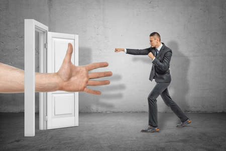 Big male open hand appearing through white doorway and businessman making kicking gesture on grey wall background