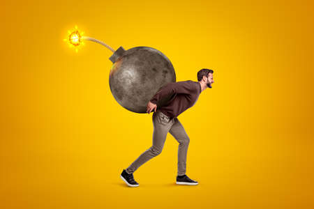 Young man in casual clothes carrying big ball bomb with fuse on his back on yellow background