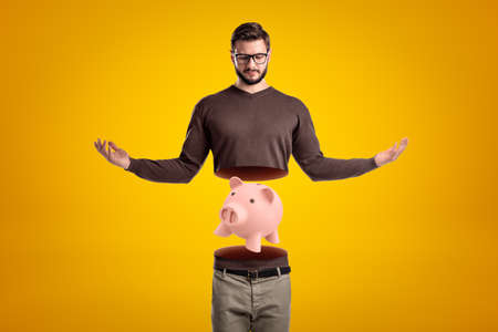 Young man in casual clothes cut in half with pink piggy bank inside on yellow background Reklamní fotografie