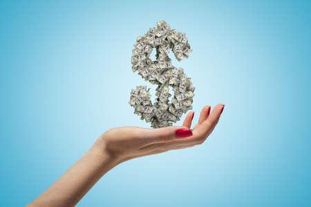 Female hand holding dollar sign on blue background Banco de Imagens