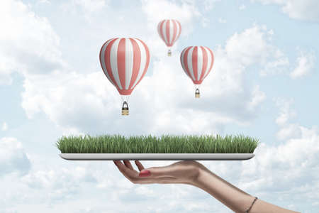 Side view of womans hand holding digital tablet with green grass on screen against sky with white clouds and three striped hot air balloons on it.