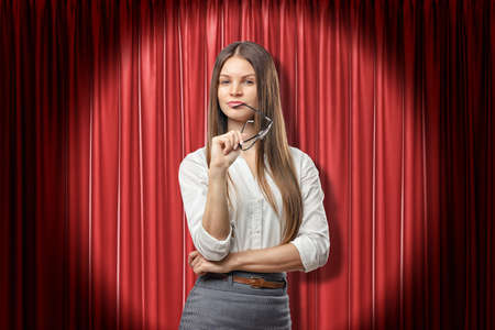 Young serious brunette business woman with glasses thinking on red stage curtains background Reklamní fotografie
