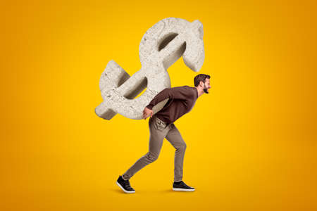 Young man in casual clothes carrying big stone dollar sign on his back on yellow background