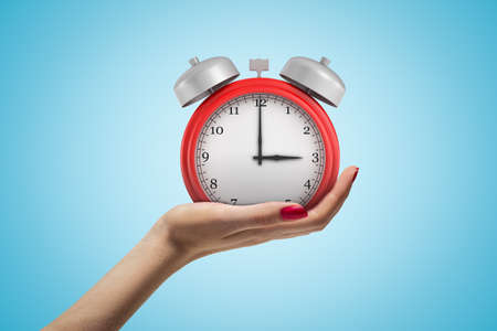 Female hand holding red alarm clock on blue background