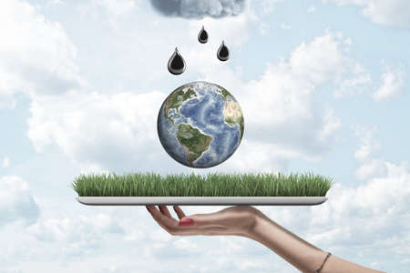 Closeup of womans hand holding digital tablet with grass on screen, little Earth in air above it and black drops falling from grey cloud above.