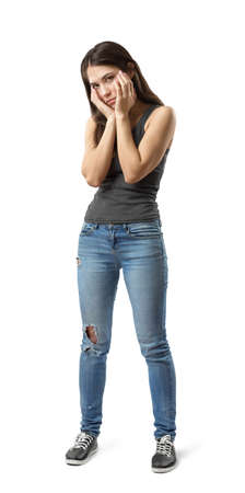 Half-turn view of young sad woman in gray sleeveless top and blue jeans standing with hands at face isolated on white background.