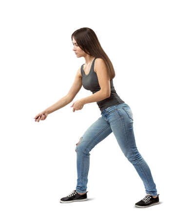 Side view of young fit woman in gray top and blue jeans bending forward slightly and posing as if holding invisible rope isolated on white background.