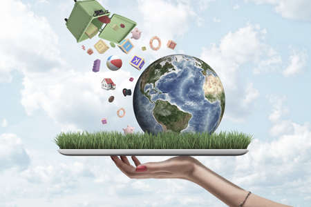 Hand holding digital tablet with grass growing on screen and little Earth on it, and bin toppled over in air from which a lot of objects are falling down. Imagens